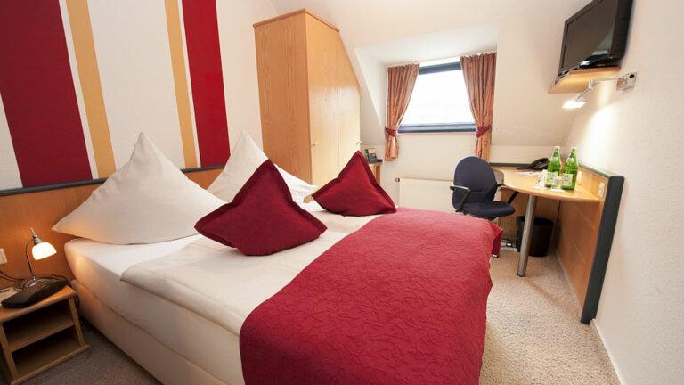 Zimmeransicht eines Doppelzimmers mit Blick zum Fenster im Hotel Eifelkern.